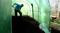 gardener work hard with soil in new greenhouse. video