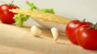 Garlic falls on a table near spaghetti and tomatoes video