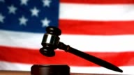 Gavel dropping on sounding block with american flag in background video