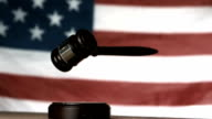 Gavel dropping onto sounding block with american flag in background video