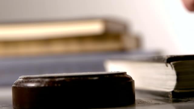 Gavel falling on sounding block beside books video