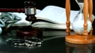Gavel falling onto sounding block beside hourglass bible and handcuffs video