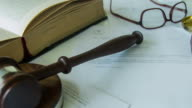 Gavel sitting on juridical paperwork contract video