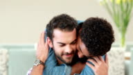 Gay couple embracing in the couch video
