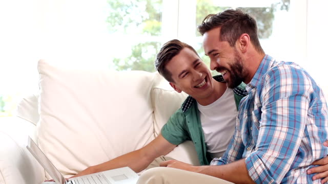Gay couple relaxing on the couch using laptop video