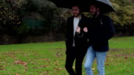 Gay couple sharing an umbrella Panning to left video