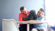 Gay couple sitting with their pet poodle video