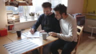 Gay couple writing and planning together video