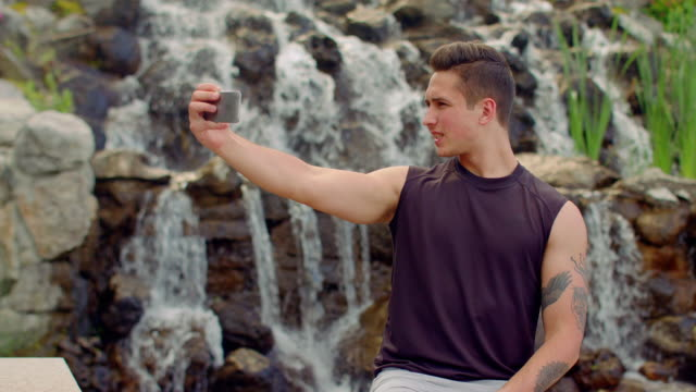 Gay taking selfie near waterfall. Man posing for selfie photo outdoor video