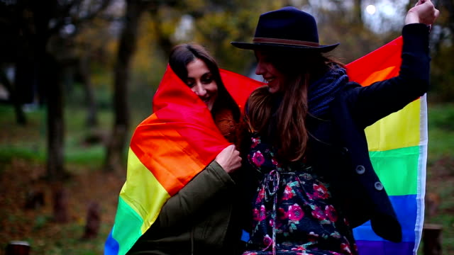 Gay Women Flirting Under Rainbow Flag in Nature video