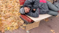 Generous young lady kindly giving charity money to poor man sleeping on bench video