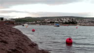 Gentle Sea Waves Lap Buoys and Sand of Shaldon Beach with view of Teignmouth Harbor video