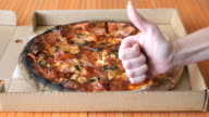 A gesture of a hand, showing fingers up over pizza video