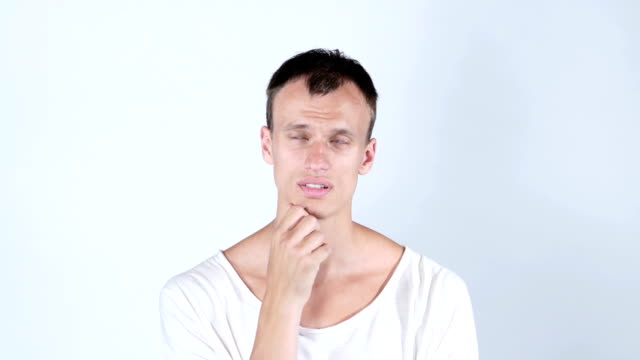 Getting idea. Smiling thoughtful handsome man standing on white background video
