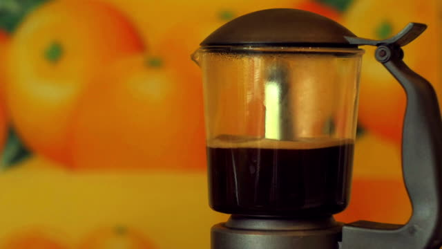 A geyser coffee maker with a glass bulb stands on gas and pours coffee. Super color, slow motion video