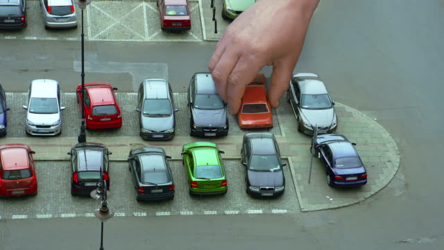 Giant hand is swapping cars on parking video