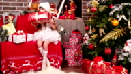 gift wrapping, a little girl lays out name cards for Christmas gifts, Santa's helper sorts the presents, the girl sitting near Christmas tree in the house video