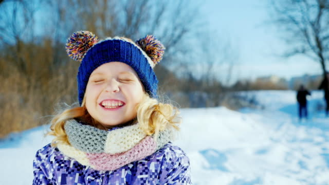 Girl 5 years enjoys a good winter day. Throws snow, laughing, positive emotions and funny faces video