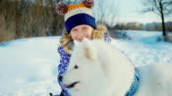 Girl 5 years old with a big white fluffy dog. Play the winter in the park, laughing girl video