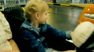 Girl 6 years old rides in an amusement park on the car. View from the car. POV video video