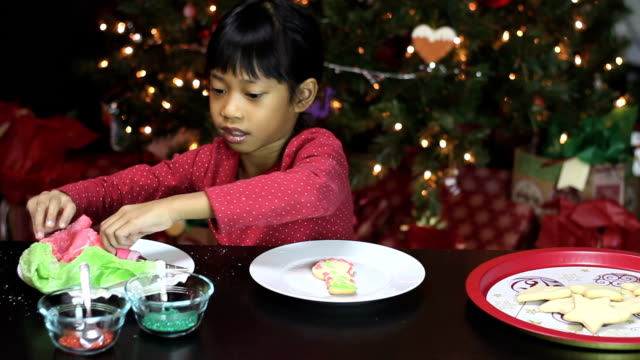 Girl Adds Red Icing To Snowman Shaped Christmas Cookie video