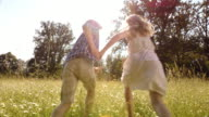 SLO MO Girl and boy holding hands running in grass video