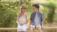 SLO MO Girl and boy sitting on footbridge splashing water video