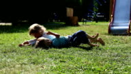 Girl and boy somersault on grass lawn video
