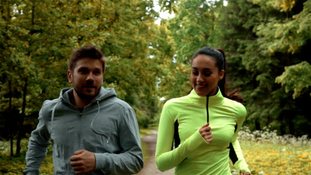 Girl and guy communicating and smiling during morning jog. They running at the park video