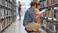 DS Girl and her dad reading a book in a library aisle video