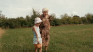 A Girl And Her Grandmother Walk The Dusty Country Road. Real People, Rural Scene. video