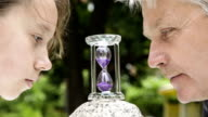 Girl and man looks at hourglasses video