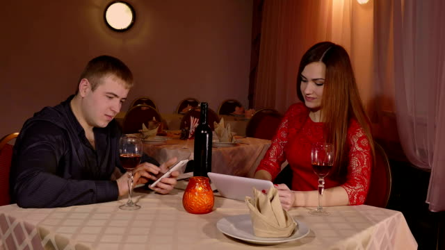 girl and man with smartphone and tablet video