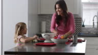 Girl and mother talking as they prepare a meal in kitchen, shot on R3D video