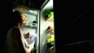 girl at night in the refrigerator. woman drinks water. video