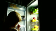 girl at night in the refrigerator. woman is drinking a beverage. video