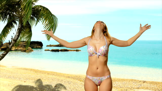 Girl blonde in swimsuit  posing near the sea and enjoys video