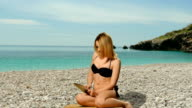 Girl blonde in swimsuit  posing near the sea and  uses a tablet video