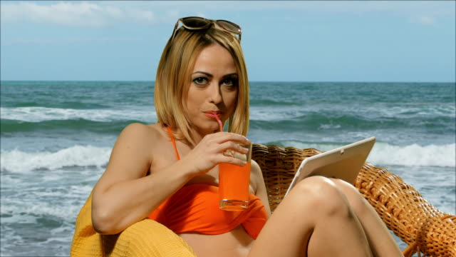 Girl blonde on the beach in swimsuit drinking juice and  uses a tablet video