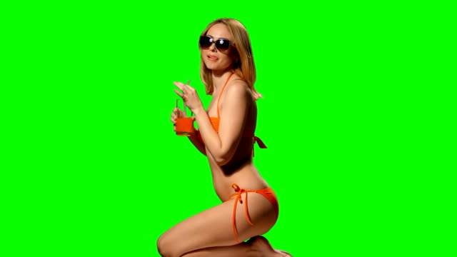 Girl blonde on the beach in swimsuit drinking juice (alpha channel) video