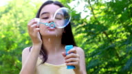 Girl blowing bubbles. slow motion video