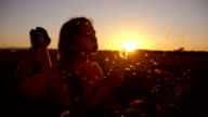 SLO MO Girl blowing dandelions at sunset video