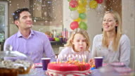 SLO MO girl blowing out the candles while confetti rain video