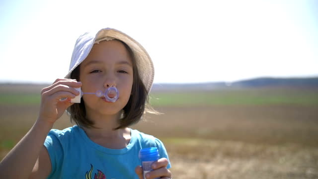 Girl Blowing Soap Bubbles Outdoors In The Field, Slow Motion video