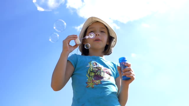 Girl Blowing Soap Bubbles Outdoors On A Sky Background, Slow Motion video