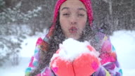 Girl blows snow towards the camera video