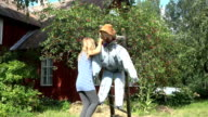 girl bring scarecrow hang on ladder on cherry tree from birds. video