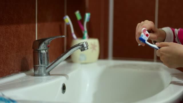Girl brushing teeth at bathroom sink video