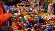 A girl buying some colorful Christmas tree balls on a Christmas market video