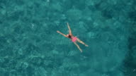 AERIAL: Girl catching a breath, submerging, swimming in transparent ocean water video